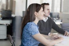Deux gens d'affaires s'asseyant à une table de conférence et écoutant au cours d'une réunion d'affaires Photo stock