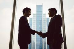 Deux gens d'affaires se serrant la main images libres de droits