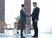Deux gens d'affaires se serrent la main dans le bureau image stock