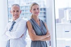 Deux gens d'affaires souriant à l'appareil-photo dans le bureau Photographie stock