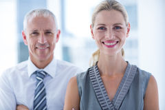 Deux gens d'affaires souriant à l'appareil-photo dans le bureau Image stock