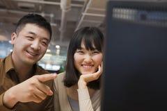 Deux gens d'affaires souriant et regardant l'ordinateur dans le bureau Photographie stock libre de droits