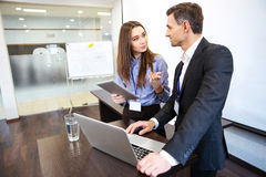Deux gens d'affaires travaillant l'ordinateur portable et le comprimé uing ensemble Images stock