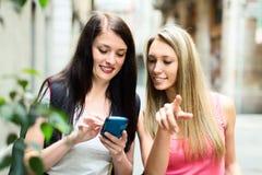 Deux gentilles filles trouvant le chemin avec le smartphone Photographie stock
