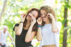 Deux girs faisant la moustache avec leurs cheveux Photo stock