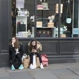 Deux gitls fatigués dans des vestes avec des paniers se reposent sur le trottoir près du magasin, attendant des amis Image libre de droits