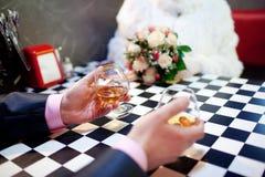 Deux glaces de cognac dans les mains du mâle Image libre de droits