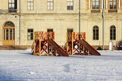 Deux glissières en bois des enfants rouges et jaunes établies sur la place devant le palais en hiver Photo stock
