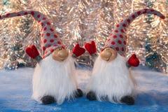 Deux gnomes gais avec des mains lèvent se poser sur un argent Images stock