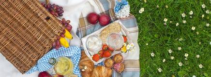 Deux gobelets de vin, fraise fraîche, miel et vin sont servis au panier picnicPicnic romantique d'été avec les pommes et le pain photographie stock libre de droits