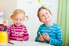 Deux gosses dessinant avec des crayons de coloration Photo stock