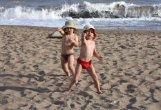 Deux gosses heureux jouant sur la plage Photos stock