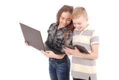 Deux gosses jouant et surfant le Web sur la tablette et l'ordinateur portatif digitaux Images libres de droits