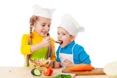 Deux gosses mangeant de la salade Image stock