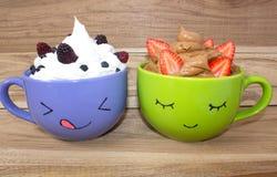 Deux grandes tasses avec les visages peints, la crème fouettée et les baies se tiennent sur une étagère en bois Mousse de chocola image libre de droits
