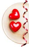Deux grands coeurs rouges d'un plat d'or d'isolement sur le blanc avec le fest Photos libres de droits