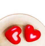 Deux grands coeurs rouges d'un plat d'or d'isolement sur le blanc avec le fest Photo stock