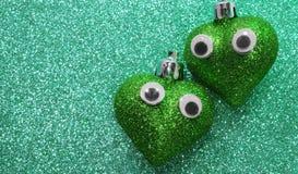 Deux grands coeurs verts dans l'amour avec des yeux à l'arrière-plan scintillent Images libres de droits