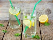 Deux grands verres de limonade froide avec de la glace, citron, feuilles en bon état Image stock