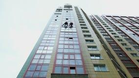 Deux grimpeurs industriels sont lavage, nettoyant la façade d'un immeuble de bureaux moderne clips vidéos