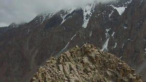 Deux grimpeurs sur la crête de la roche La neige de observation de femme a couvert des montagnes Silhouette d'homme se recroquevi clips vidéos