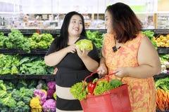 Deux grosses femmes achetant les légumes frais Photo stock