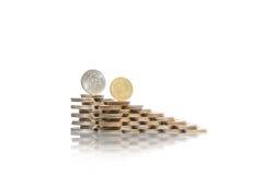 Deux groupes croissants de piles des pièces de monnaie avec le rouble russe et la pièce de monnaie ukrainienne sur le dessus Images stock