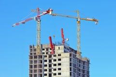 Deux grues stationaty plus de sur un bâtiment d'un skyscrape dans l'avant Photo libre de droits