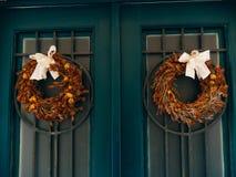Deux guirlandes brunes avec des arcs sur les portes vertes Image stock