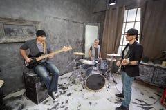 Deux guitaristes et jeux de batteur dans la chambre Image stock