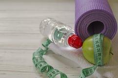 Deux haltères, bouteille de l'eau, pomme verte, centimètre sur le blanc images stock