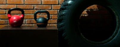 Deux haltères différentes sur un fond de mur de briques dans un gymnase de crossfit image stock
