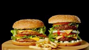 Deux hamburgers de boeuf de métier sur la table en bois d'isolement sur le fond foncé de gamme de gris clips vidéos