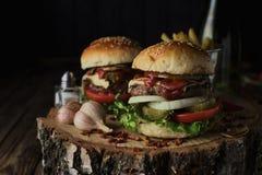 Deux hamburgers de boeuf sur un fond foncé Image libre de droits