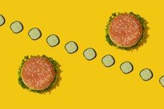 Deux hamburgers malsains frais savoureux avec le ketchup et les légumes sur le fond lumineux vibrant jaune Vue supérieure avec la photos stock