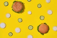 Deux hamburgers malsains frais savoureux avec le ketchup et les légumes sur le fond lumineux vibrant jaune Vue supérieure avec la photographie stock