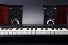 Deux haut-parleurs et plans rapprochés audio stéréo de clés de piano sur le backgro foncé Images libres de droits