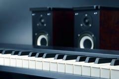 Deux haut-parleurs et plans rapprochés audio stéréo de clés de piano sur le backgro foncé Photos stock