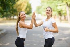 Deux heureux, belles filles dans les vêtements de sport posant sur un fond naturel Concept d'amitié Copiez l'espace Images stock