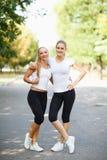 Deux heureux, belles filles dans les vêtements de sport posant sur un fond naturel Concept d'amitié Copiez l'espace Image stock