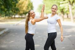 Deux heureux, belles filles dans les vêtements de sport posant sur un fond naturel Concept d'amitié Copiez l'espace Image libre de droits