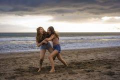 Deux heureux et jeunes amies ou soeurs chinoises asiatiques attirantes de femmes ayant l'amusement jouant la lutte sur la plage d images libres de droits
