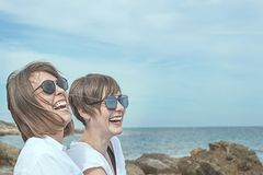 Deux heureux, filles de sourire sur la plage Sensation de joie entre deux amis Image libre de droits