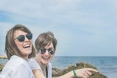 Deux heureux, filles de sourire sur la plage Sensation de joie entre deux amis Photos stock