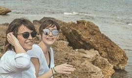 Deux heureux, filles de sourire sur la plage Sensation de joie entre deux amis Image stock