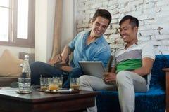Deux hommes à l'aide de la tablette au café, amis Images libres de droits