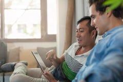 Deux hommes à l'aide de la tablette au café, amis Images stock
