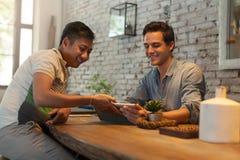 Deux hommes à l'aide de la tablette au café de Tableau Image libre de droits
