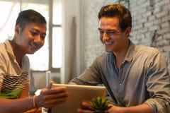 Deux hommes à l'aide de la tablette au café de Tableau Photos stock