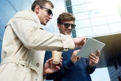Deux hommes à l'aide de la Tablette au soleil Photos stock